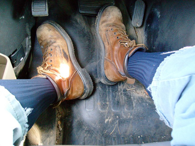a man wearing a pair of work boots inside a vehicle