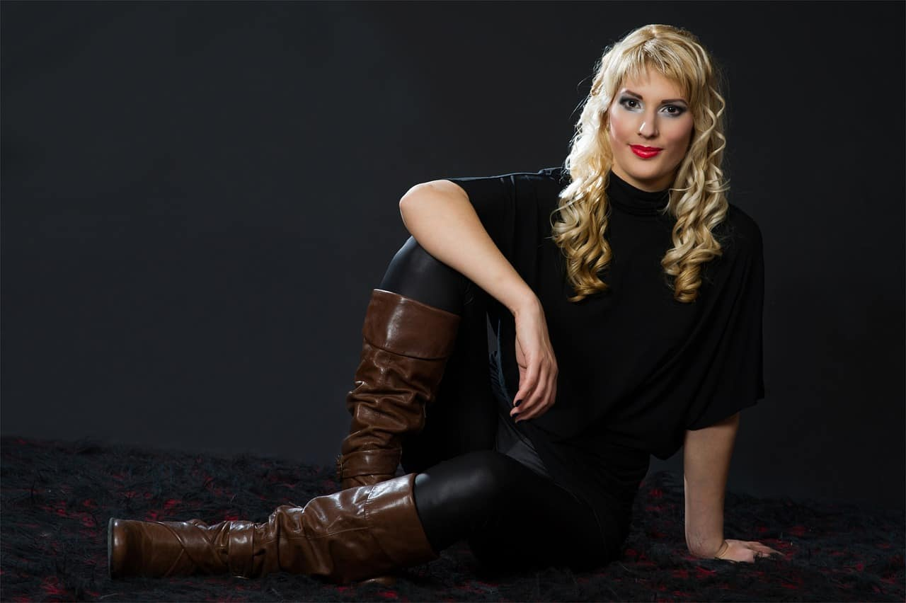 Woman wearing a brown leather boots sitting on the floor